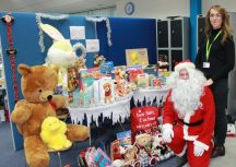 Supported tenancy officer Rebecca Holden with Father Christmas with the mountain of donated toys and gifts.