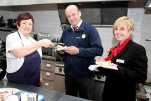 Compton Hospice kitchen supervisor Brenda Chester thanks Redrow for their support by serving up tasty treats to Dave Dodd & Jenny Atkinson.
