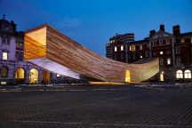 The Smile illuminated at night , seen from the west side of the parade ground. Photo by Dav Stewart. AHEC. Alison Brooks Architects. Arup.