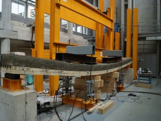 "An 8 meter long timber and wood-cement composite slab is tested to rupture at the School of Engineering and Architecture Fribourg within a project of the National Research Programme 66 ""Resource Wood"". Although weighing only a third of an equally performing regular concrete slab, this new type of composite could, in principle, be used in residential and office buildings."